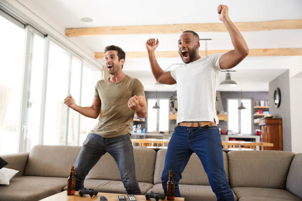 Two Excited Male Friends Celebrate Watching Sports On Television stock photo