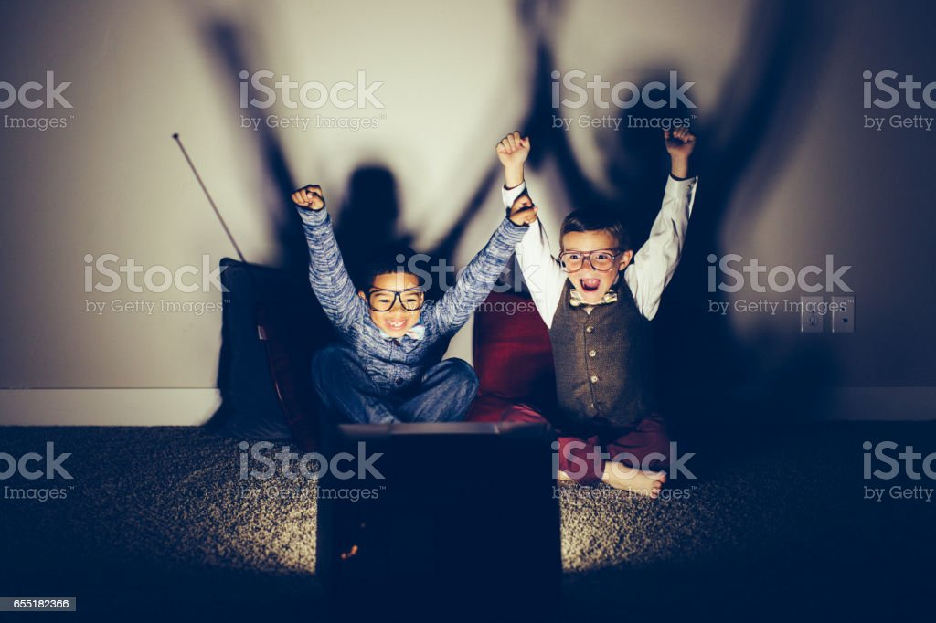 Two Excited Young Nerds Watching Sporting Event on Television stock photo
