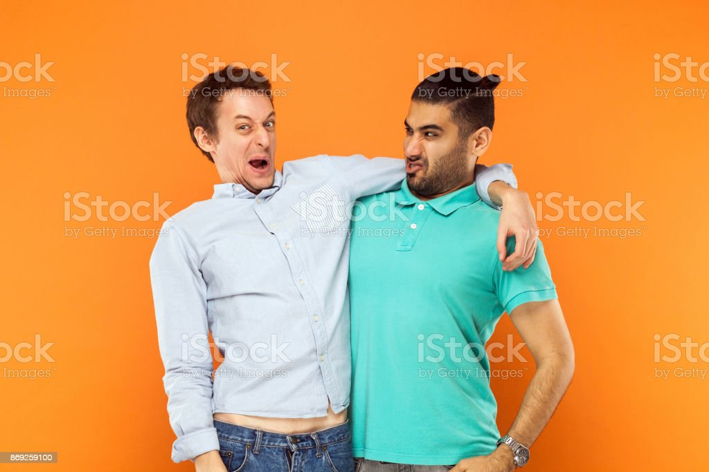 Two expressive comic, hugging and grimacing at camera. stock photo