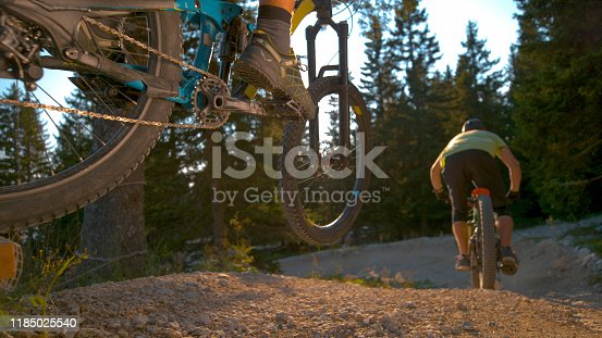 CLOSE UP, LOW ANGLE, DOF: Two extreme mountain bike riders speed along an empty gravel track in the green forest. Cool action shot of unrecognizable friends racing on high tech electric bicycles.