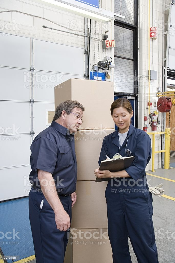Two factory workers looking at a clipboard stock photo