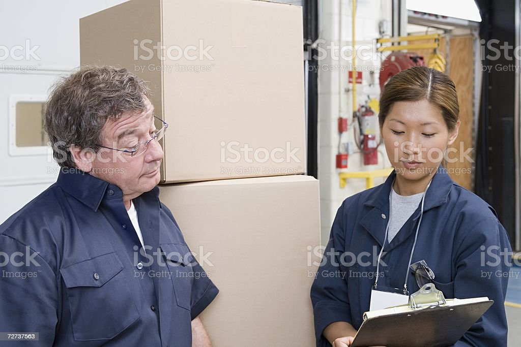 Two factory workers looking at clipboard stock photo