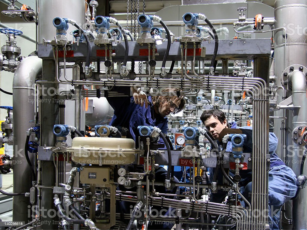 Two factory workers looking at mechanics of a large machine stock photo