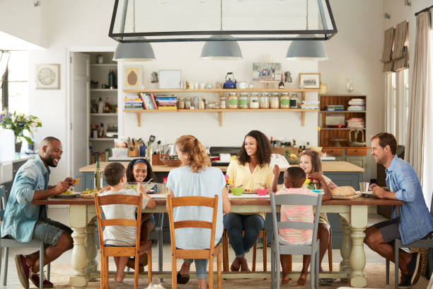 Two families having lunch together in the kitchen at home Two families having lunch together in the kitchen at home dining table stock pictures, royalty-free photos & images