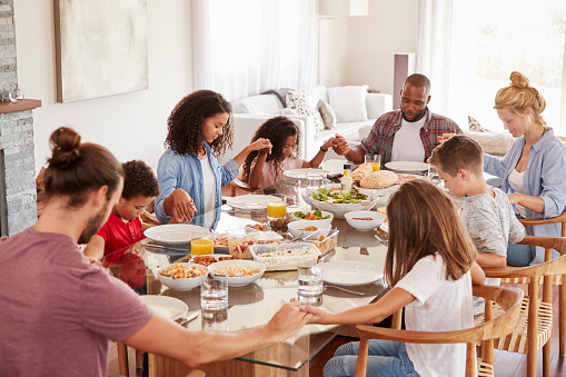 istock Two Families Praying Before Enjoying Meal At Home Together 976810664