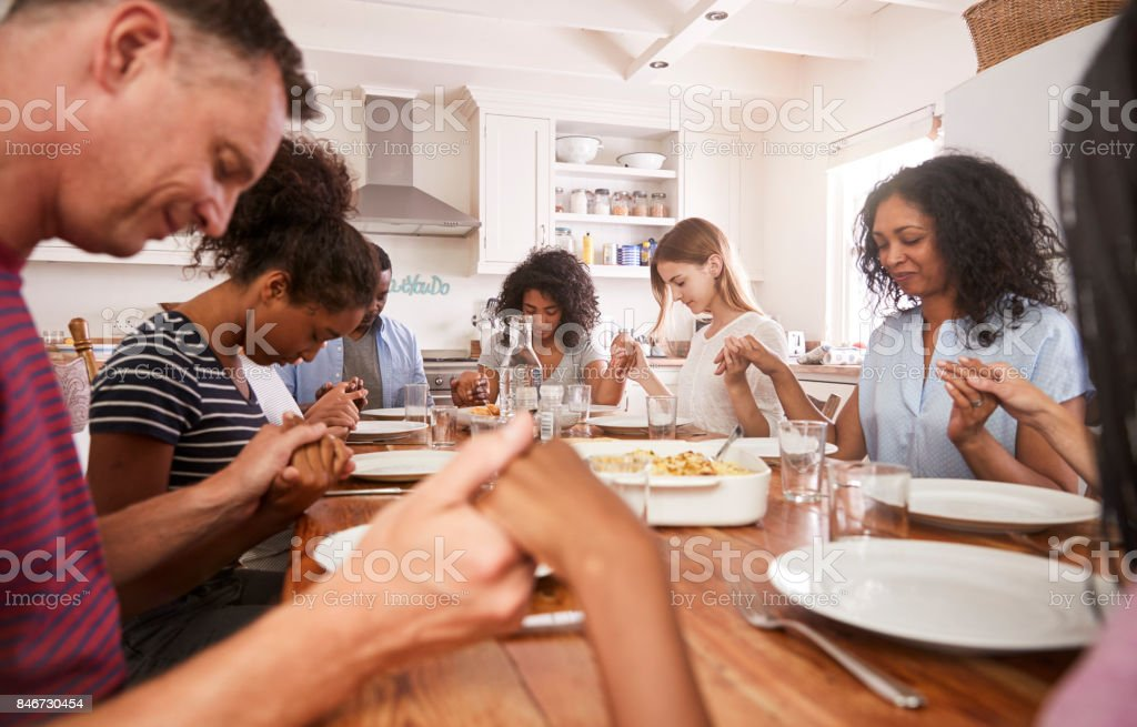 Two Families Saying Grace Before Eating Meal Together stock photo