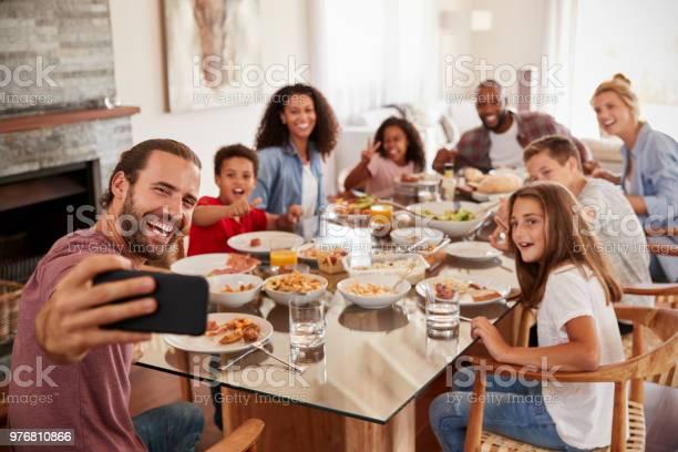 Two families taking selfie as they enjoy meal at home together picture id976810866?b=1&k=6&m=976810866&s=612x612&h=jivsjw6r63uwdljlbgb8qmc74ecwtivwvmxdcqk5aj8=