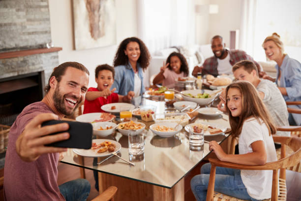 two families taking selfie as they enjoy meal at home together - family dinner stock photos and pictures