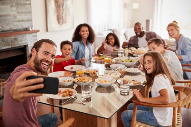 Dos familias tomando Selfie mientras disfruta de comida en casa juntos - foto de stock
