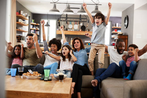 Deux familles de regarder les Sports à la télévision et acclamations - Photo