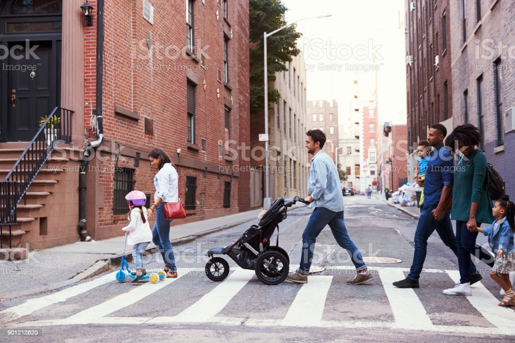 Two families with daughters crossing road royalty-free stock photo