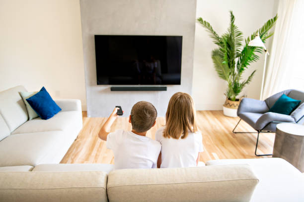 A two family brother and sister holding remote control and watching TV show. Back view stock photo
