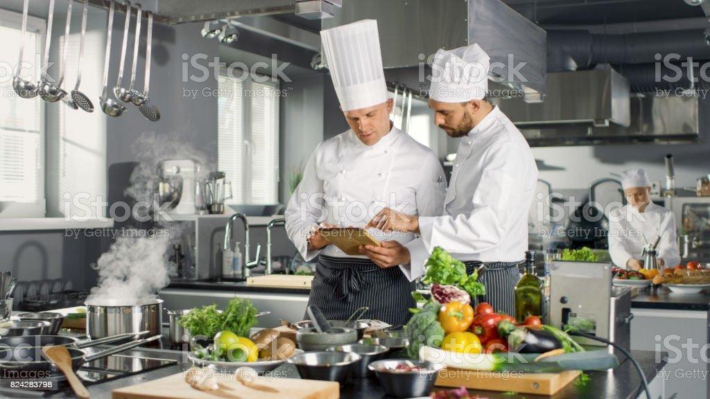 Dos Chefs famosos discutan su vídeo Blog mientras uso de Tablet PC. Trabajan en una cocina profesional grande restaurante de acero inoxidable. - foto de stock