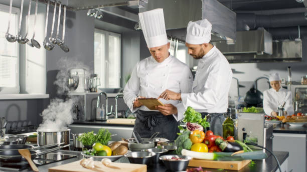 Two Famous Chefs Discuss Their Video Blog while Using Tablet Computer. They Work on a Big Restaurant Stainless Steel Professional Kitchen. stock photo