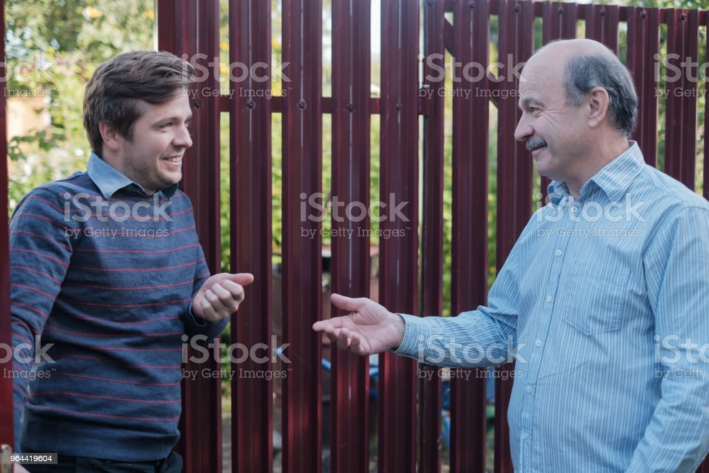 two farmers takling to each other on sunny day. They discuss important news foto stock royalty-free