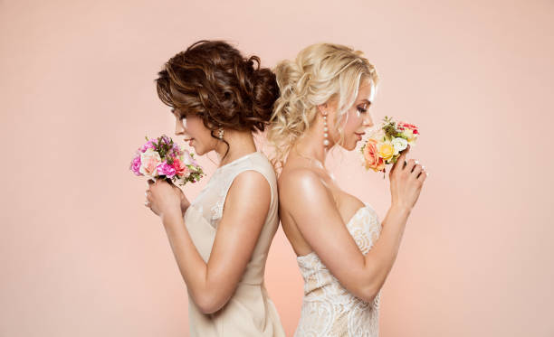 Two Fashion Models with Flowers Bouquet Beauty Portrait, Beautiful Women Studio Shot stock photo