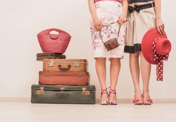 zwei modisch gekleideten frauen posiert auf die koffer im retro-stil - damenschuhe 44 stock-fotos und bilder