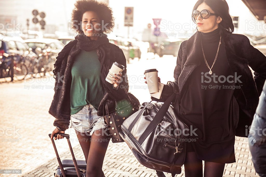 Two fashionable women walking out of the airport stock photo