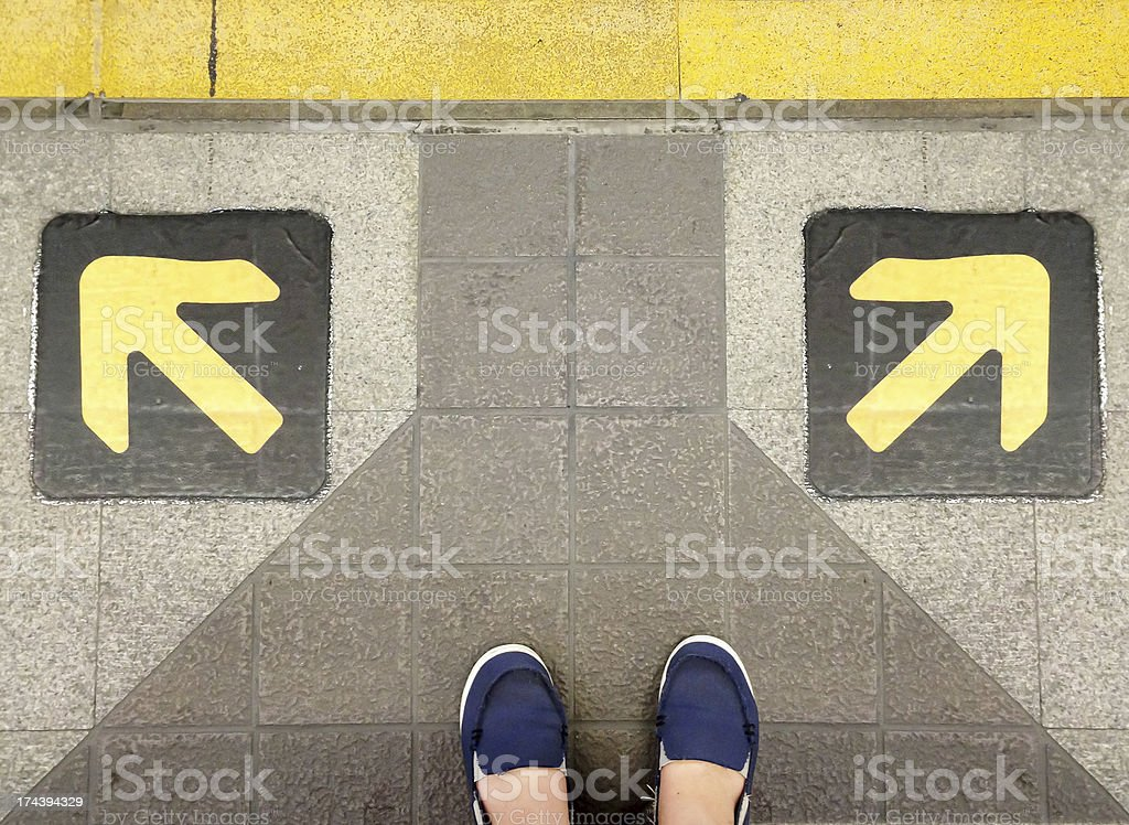 Two feet behind arrows in opposite directions stock photo