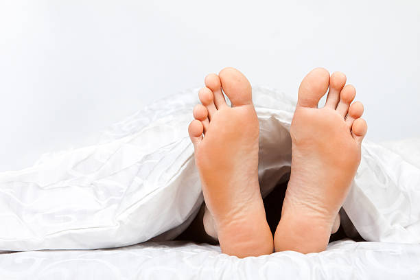 Two feet poking out from under a duvet A man's feet poke out of the bottom of a white duvet in bed sole of foot stock pictures, royalty-free photos & images