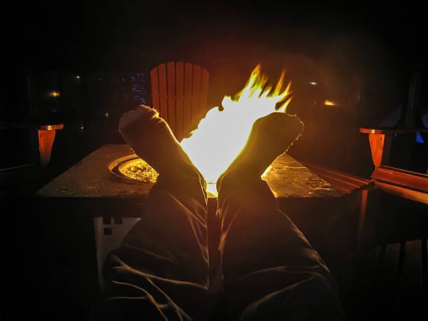 zwei füße entspannen am kamin im freien - gaskamin stock-fotos und bilder