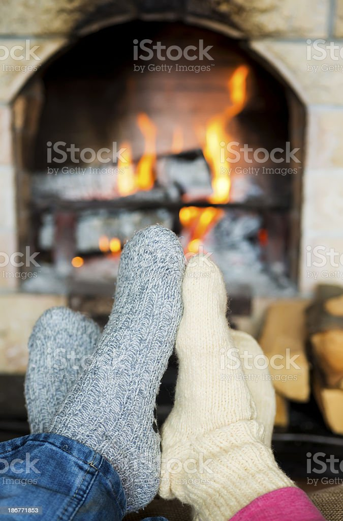 Two feet warming up in front of the fire stock photo