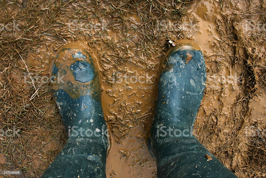 Two feet wearing rain boots standing in the mud stock photo