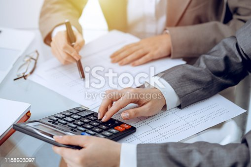 istock Two female accountants counting on calculator income for tax form completion hands close-up. Business and audit concept. 1158603097