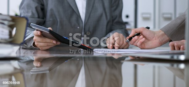 istock Two female accountants counting on calculator income for tax form completion, hands closeup. Internal Revenue Service inspector checking financial document. Planning budget, audit  concept 696264448
