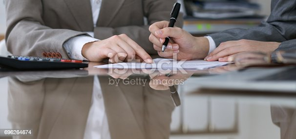 istock Two female accountants counting on calculator income for tax form completion, hands closeup. Internal Revenue Service inspector checking financial document. Planning budget, audit  concept 696264674