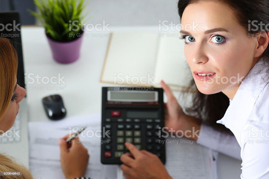 Duas mulheres contabilistas contando com Calculadora - foto de acervo