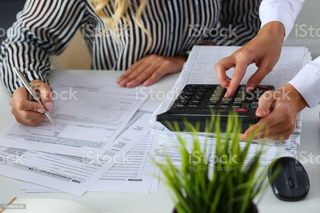 Two female accountants counting on calculator stock photo