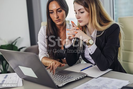 istock Two female accountants working together on financial report using laptop sitting at desk in account department 890882632