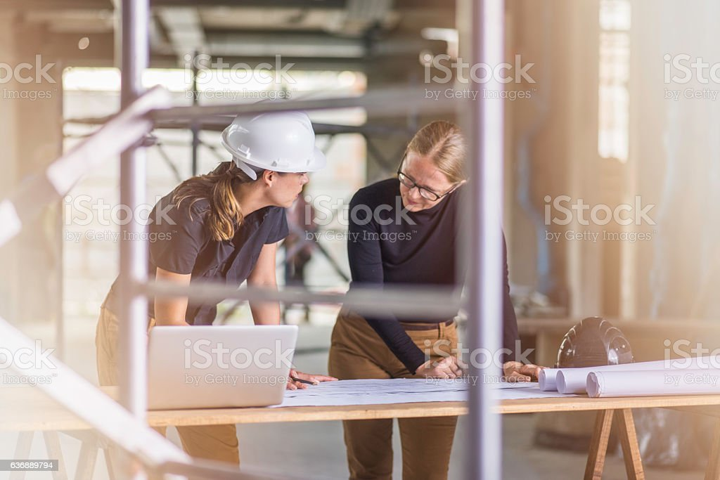 Two female architects reviewing blueprints – Foto