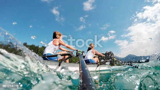 istock Two female athletes rowing across lake in late afternoon 861214118