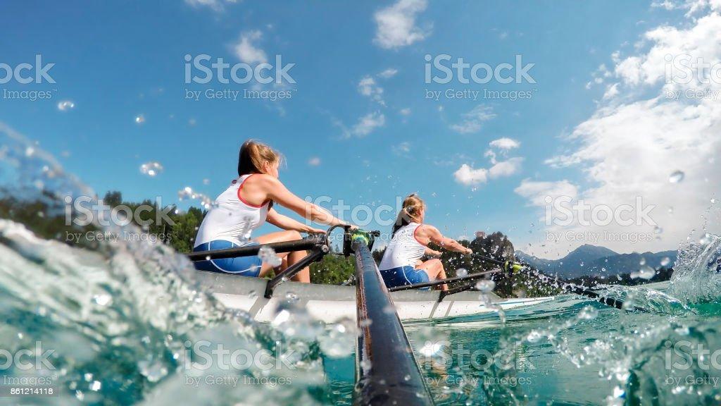Dois atletas do sexo feminino remo lago no fim da tarde - foto de acervo