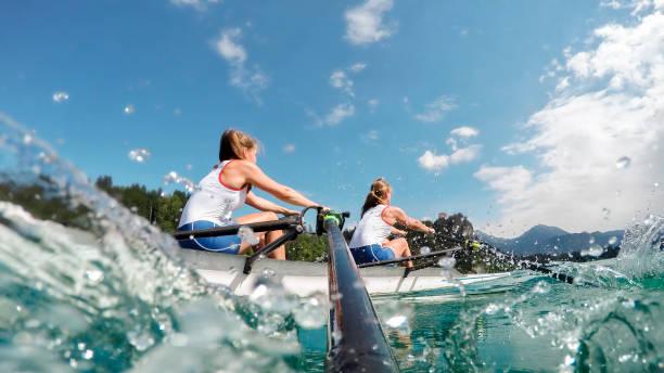 Dos atletas de remo en el lago en la tarde - foto de stock