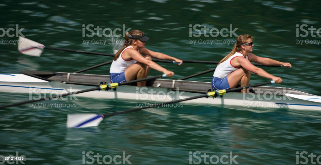Two female athletes rowing across lake in late afternoon stock photo