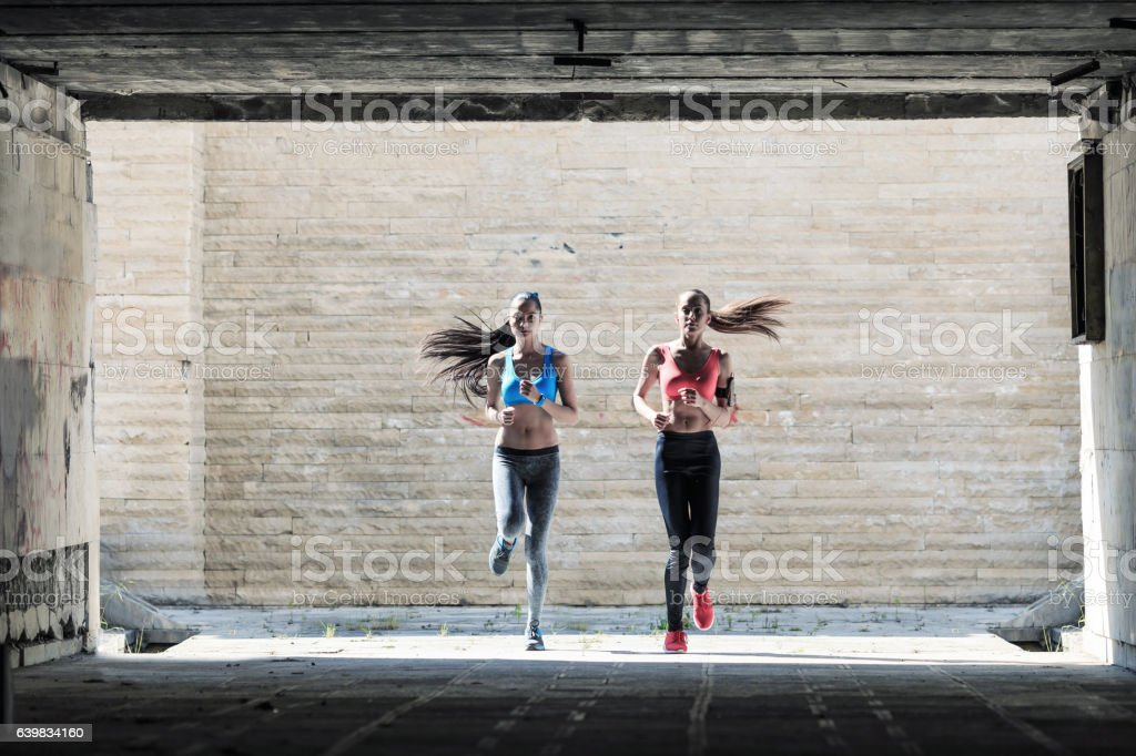 Two female athletes running in underpass stock photo