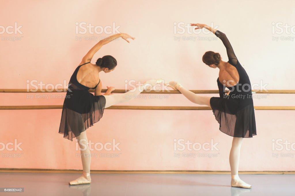 Deux danseurs de ballet féminin posant à côté d'une barre. - Photo
