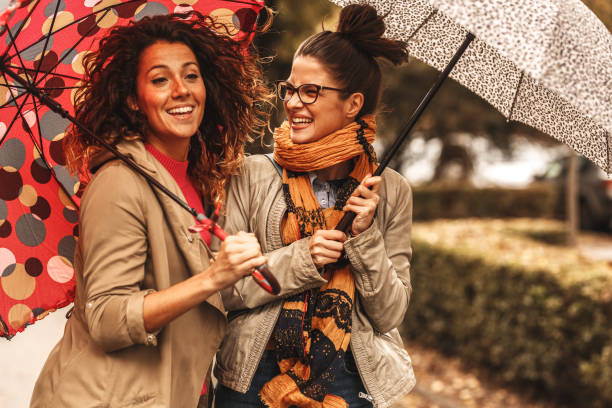 Two female best friend walks at the city street with umbrellas above head. stock photo