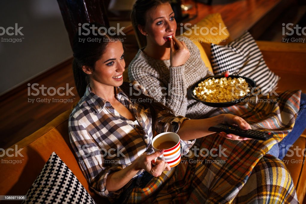 Two female best friends sitting at home on pleasant evening and watching a television show. stock photo