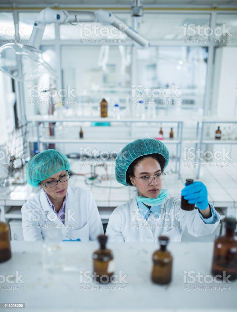 Two female biochemists analyzing chemical substances in laboratory. stock photo