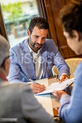 Two female business partners making their customer put his signature during a meeting in a cafeteria.
