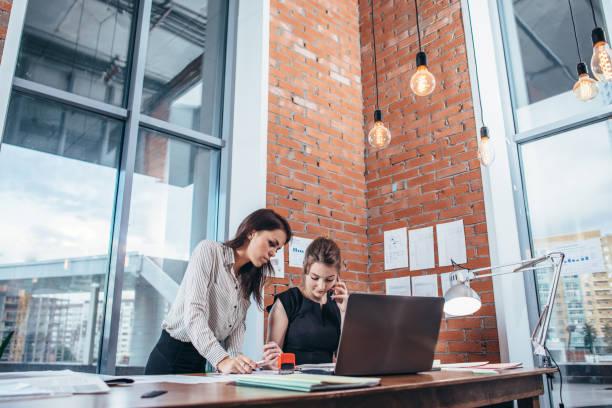 Zwei Kolleginnen im Büro arbeiten zusammen. – Foto