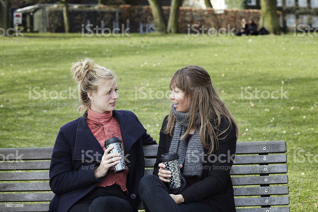 Two female college students sitting in a park with coffee royalty-free stock photo