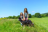 Two female cousins in countryside with their dog