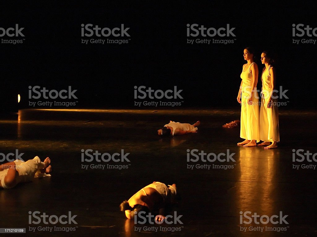 Two female dancers pause on a dark stage with fallen dancers royalty-free stock photo