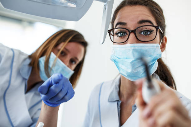 Two female dentist in dental office examining patient teeth. stock photo