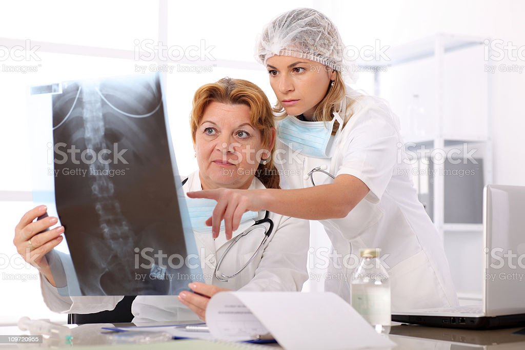 Two female doctors looking at x-ray image in the lab. royalty-free stock photo